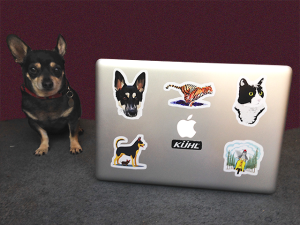 Dog posing with Redbubble stickered MacBook Pro laptop