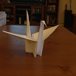 Origami crane sitting on a wooden table